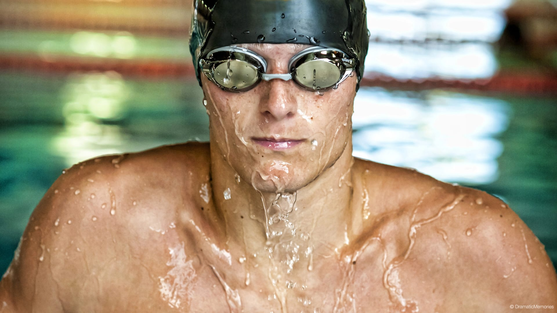 swimmer in goggles coming out of water