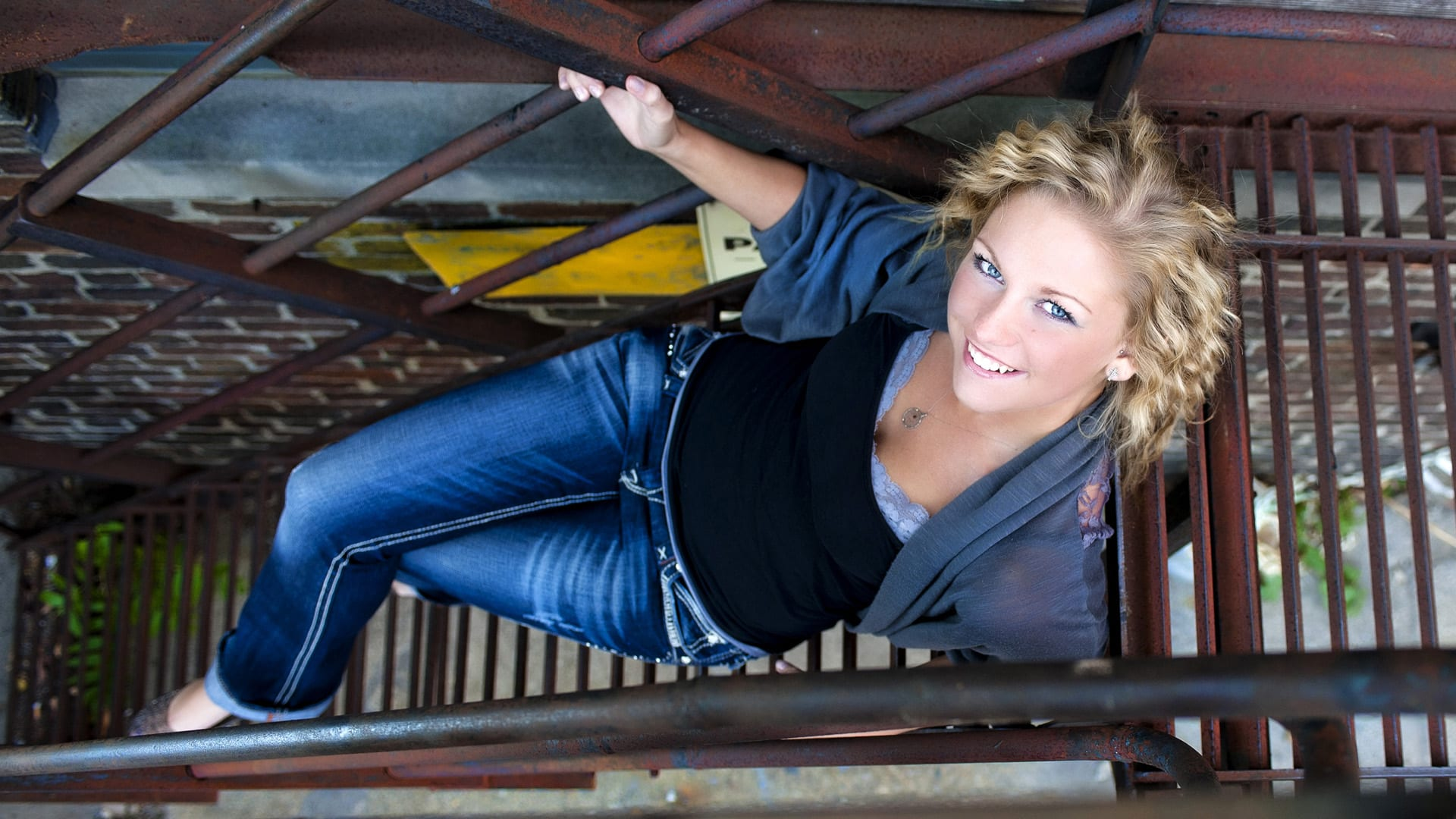 senior girl posing on a rusty fire escape in the city
