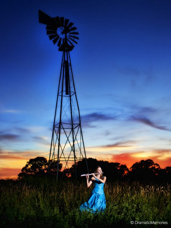 a musician playing her flute near an old windmill at sunset