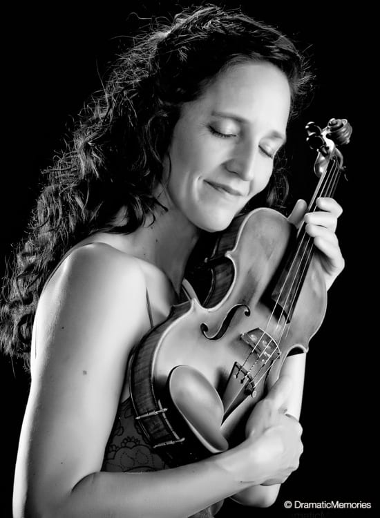 black and white image of a musician caressing her violin